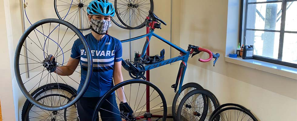 female cyclist standing in front of bicycle wheels with mask on