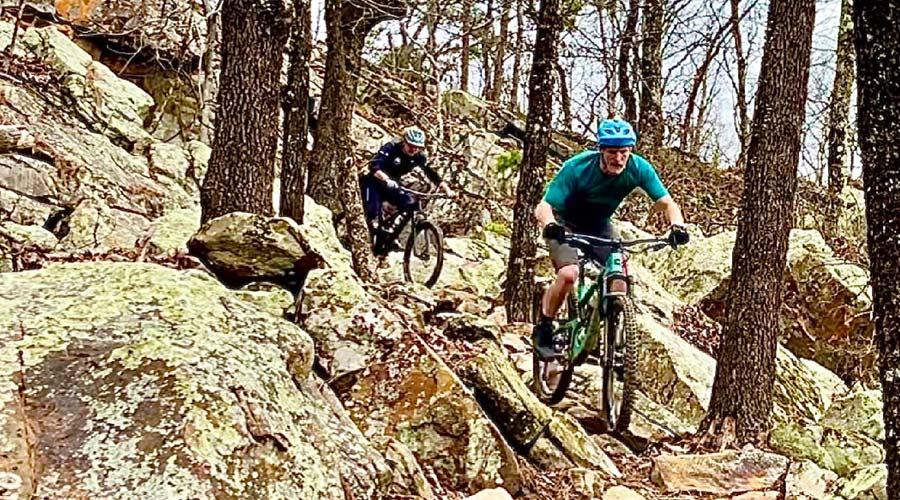 mountain bikers riding over rock field