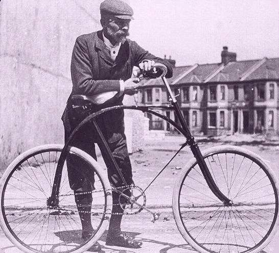 cyclist standing next antique bike