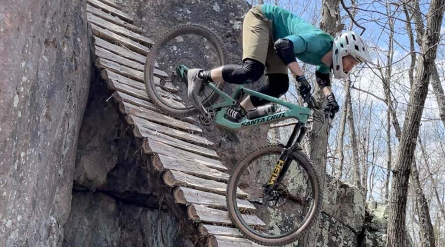 mountain biker riding down a steep wood ramp